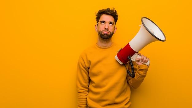 Jeune homme tenant un mégaphone fatigué et ennuyé