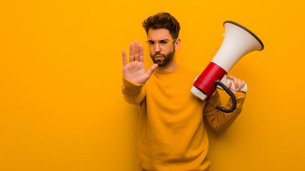 Jeune homme tenant un mégaphone, mettant la main devant