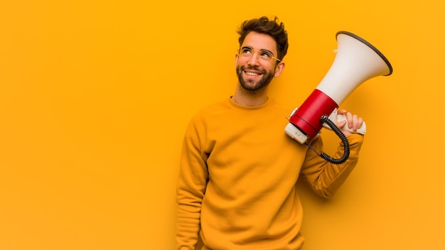 Jeune homme tenant un mégaphone rêvant d'atteindre les objectifs et les buts