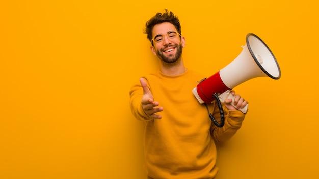 Jeune homme tenant un mégaphone tendre la main pour saluer quelqu'un