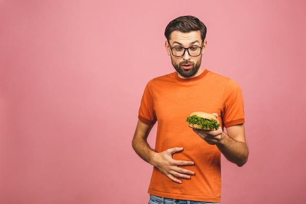 Jeune homme tenant un morceau de hamburger