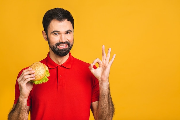 Jeune homme tenant un morceau de sandwich. l'élève mange de la restauration rapide. le hamburger n'est pas une nourriture utile.