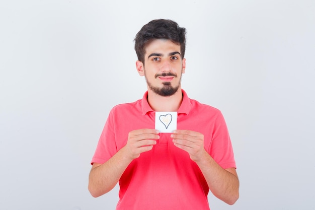 Jeune homme tenant une note collante en t-shirt et l'air mignon, vue de face.