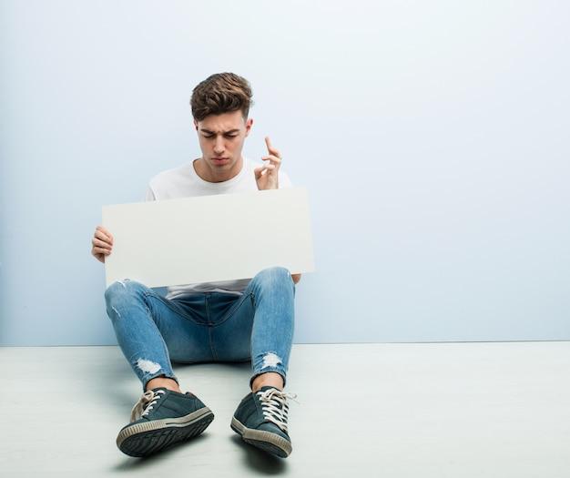 Jeune homme tenant une pancarte assise sur son sol, croisant les doigts pour avoir de la chance