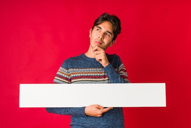 Jeune homme tenant une pancarte à côté avec une expression douteuse et sceptique.