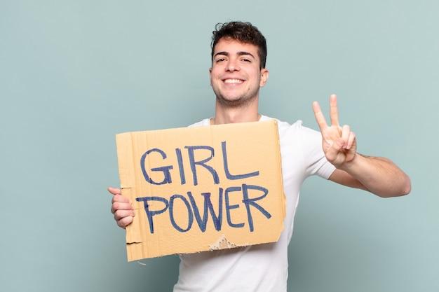 Jeune homme tenant une pancarte avec texte: girl power. concept de féminisme