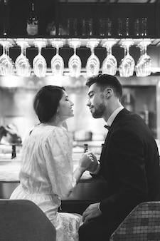 Jeune homme tenant par la main avec une femme et assis au comptoir