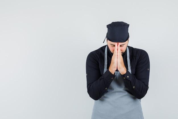 Jeune homme tenant par la main en signe de prière en chemise, tablier et à la recherche d'espoir. vue de face.