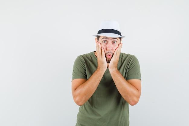 Jeune homme tenant des paumes sur les joues en t-shirt vert et chapeau et à la surprise