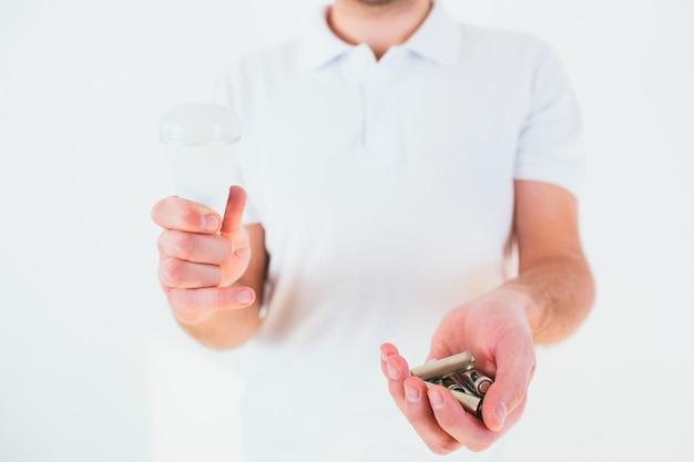 Jeune homme tenant des piles dans ses mains. temps de recyclage. métal lithium sans vie.