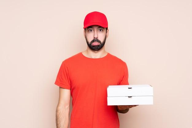 Jeune homme tenant une pizza avec une expression triste et déprimée