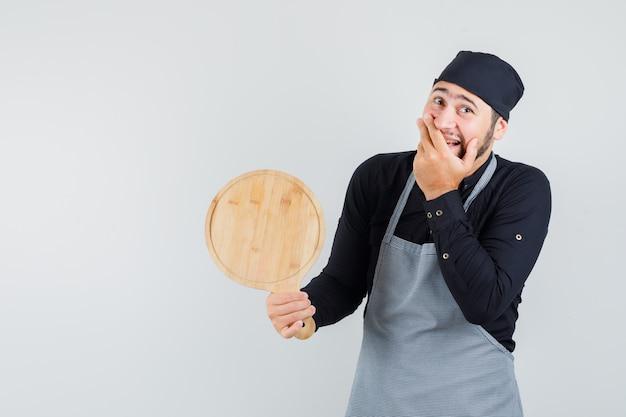Jeune homme tenant une planche à découper avec la main sur la bouche en chemise, tablier et air heureux. vue de face.