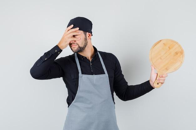 Jeune homme tenant une planche à découper avec la main sur le visage en chemise, tablier, vue de face.