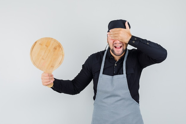 Jeune homme tenant une planche à découper avec la main sur les yeux en chemise, tablier et air heureux. vue de face.