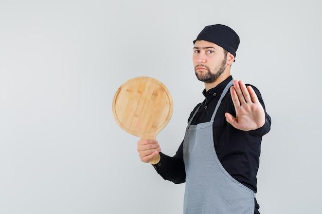 Jeune homme tenant une planche à découper avec panneau d'arrêt en chemise, tablier et à la recherche de sérieux. vue de face.