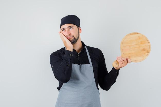 Jeune homme tenant une planche à découper avec paume sur la joue en chemise, tablier et à la pensif. vue de face.