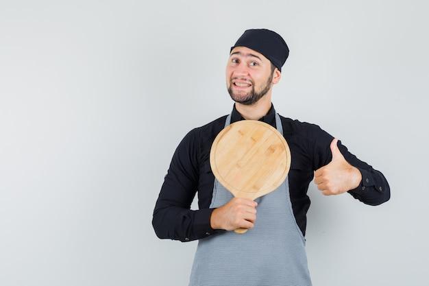 Jeune homme tenant une planche à découper avec le pouce vers le haut en chemise, tablier et à la joyeuse. vue de face.