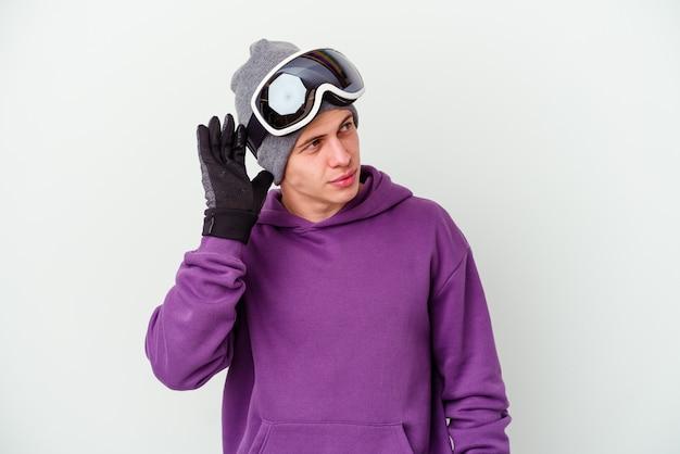 Jeune homme tenant une planche de snowboard sur blanc essayant d'écouter un commérage.