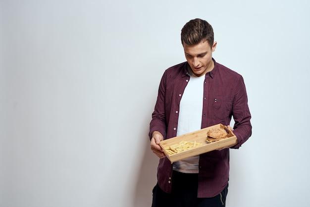 Jeune homme tenant un plateau de malbouffe