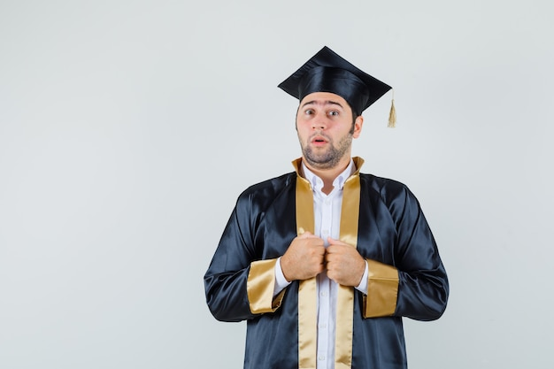 Jeune homme tenant les poings sur sa robe en uniforme d'études supérieures et à la perplexité. vue de face.