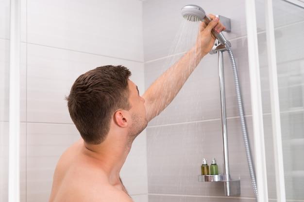 Jeune homme tenant une pomme de douche avec de l'eau qui coule dans une cabine de douche avec des portes en verre transparent dans la salle de bain