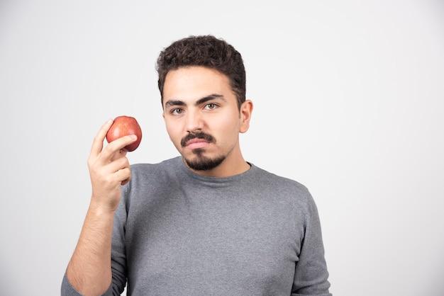 Jeune homme tenant une pomme rouge en colère.