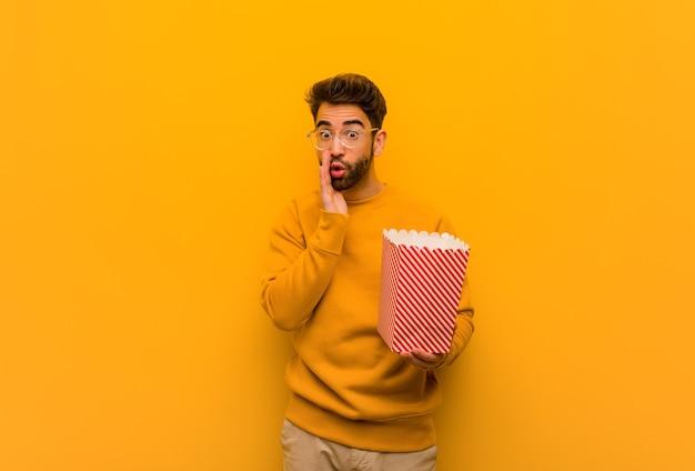 Jeune homme tenant des pop-corn chuchotant des potins
