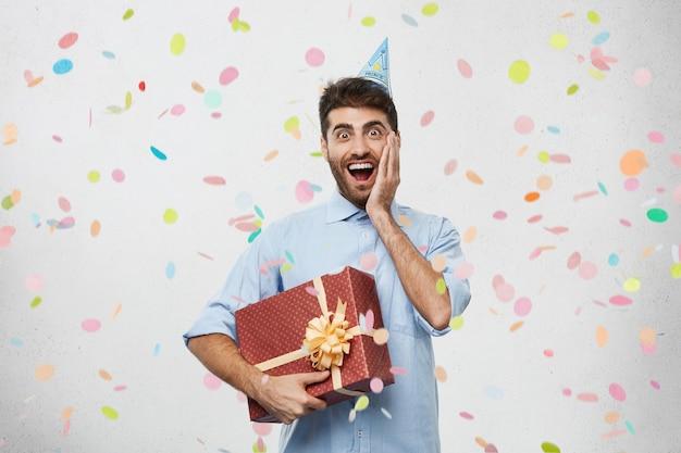 Jeune homme tenant présent entouré de confettis