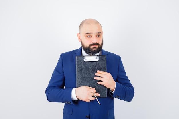 Jeune homme tenant le presse-papiers en chemise blanche, veste et à l'air pensif. vue de face.