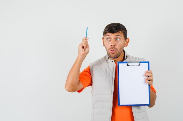 Jeune homme tenant le presse-papiers et le crayon en t-shirt, veste et à la réflexion. vue de face.