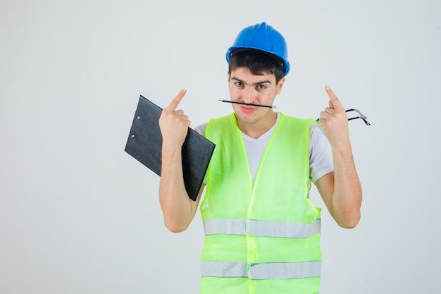 Jeune homme tenant un presse-papiers et des lunettes de sécurité dans les mains, tenant un stylo avec la bouche