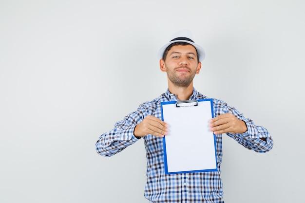 Jeune homme tenant le presse-papiers et souriant en chemise à carreaux