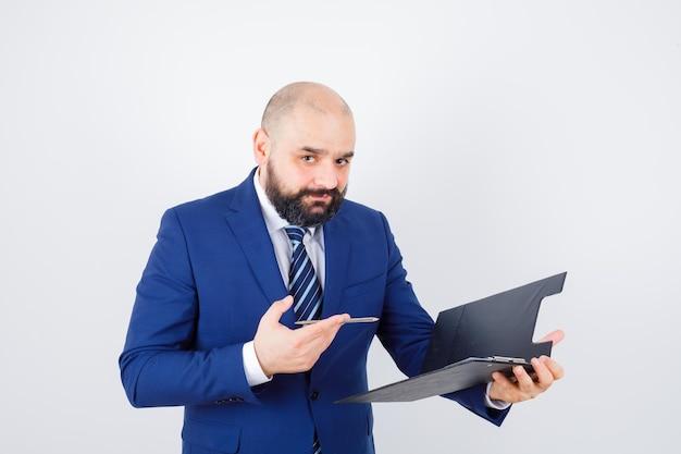 Jeune homme tenant un presse-papiers, un stylo en chemise blanche, une veste et l'air confiant, vue de face.