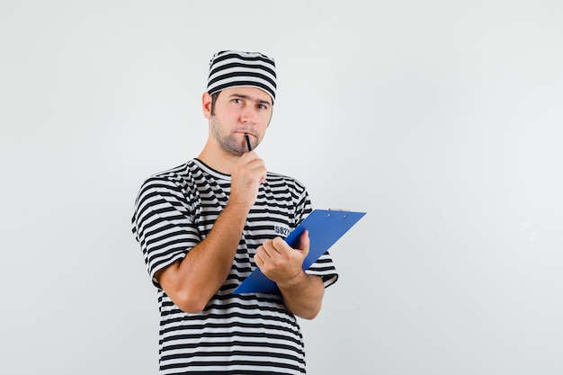 Jeune homme tenant le presse-papiers, stylo en t-shirt, chapeau et regardant pensif, vue de face.