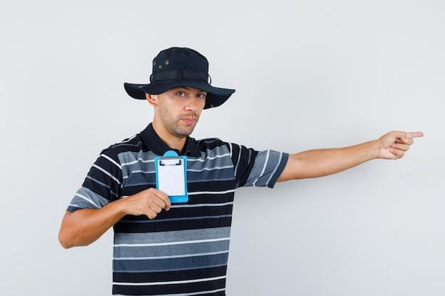 Jeune homme tenant le presse-papiers tout en pointant sur le côté en t-shirt, vue de face de chapeau.