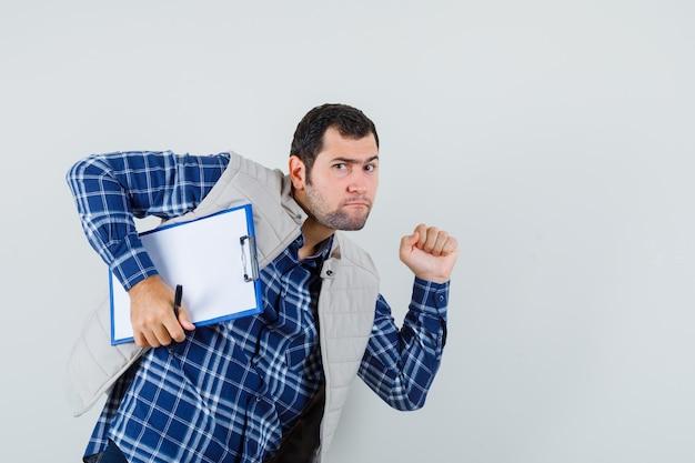 Jeune homme tenant le presse-papiers tout en se dépêchant en chemise, veste et à la vue alarmée, de face.