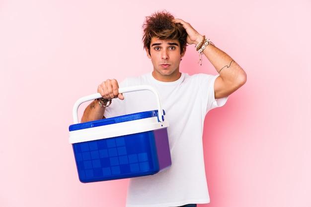 Jeune homme tenant un réfrigérateur portable étant choqué