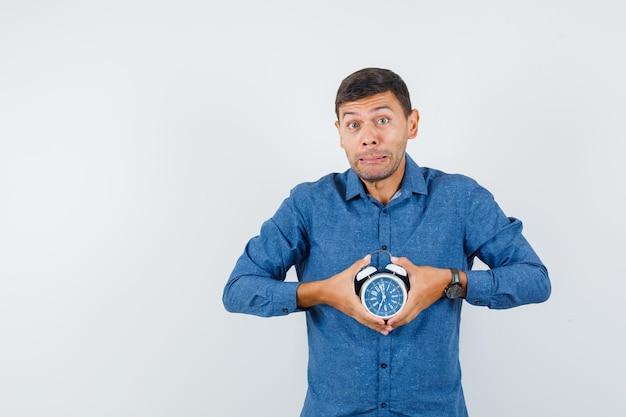 Jeune homme tenant un réveil en chemise bleue et l'air inquiet. vue de face.