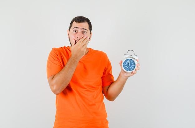 Jeune homme tenant un réveil avec la main sur la bouche en t-shirt orange et l'air troublé. vue de face.