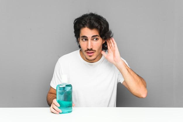 Jeune homme tenant un rince-bouche essayant d'écouter un potin.