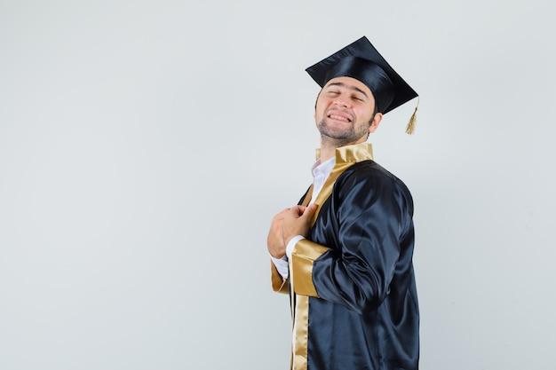Jeune homme tenant sa robe en uniforme d'études supérieures et à la recherche de calme.
