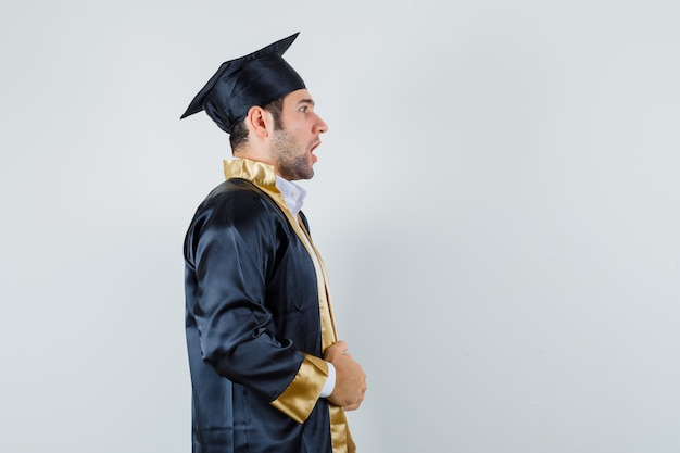 Jeune homme tenant sa robe en uniforme d'études supérieures et à la surprise.