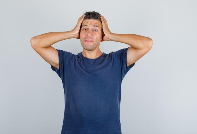 Jeune homme tenant sa tête avec les mains en t-shirt bleu foncé et à la vue de face, stressant.