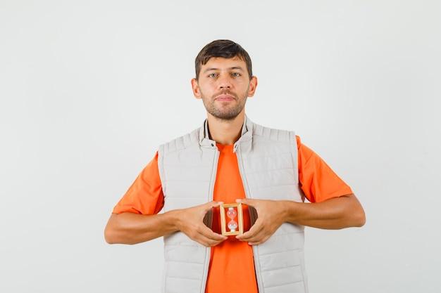 Jeune homme tenant un sablier et souriant en t-shirt, veste, vue de face.