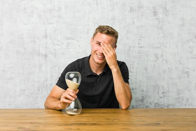Jeune homme tenant un sablier sur une table couvre les yeux avec les mains, sourit largement en attendant une surprise.