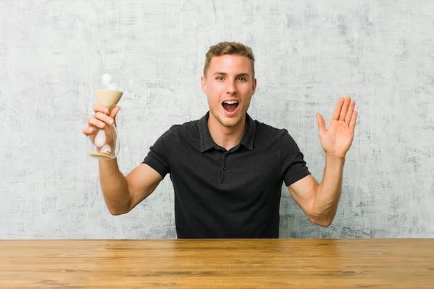 Jeune homme tenant un sablier sur une table recevant une agréable surprise, excité et levant les mains