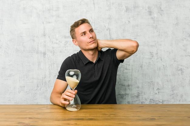 Jeune homme tenant un sablier sur une table touchant l'arrière de la tête, en pensant et en faisant un choix.