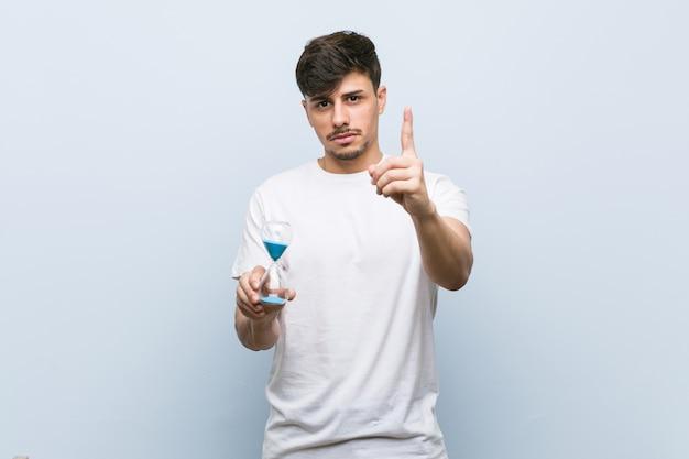 Jeune homme tenant un sablier