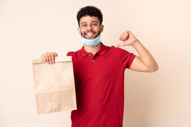 Jeune homme tenant un sac de nourriture à emporter fier et satisfait de soi