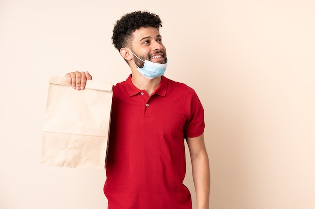 Jeune homme tenant un sac de nourriture à emporter à la recherche en souriant